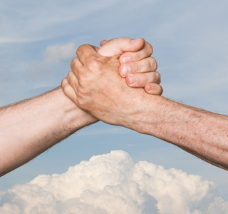 Shaking hands of two male people against the blue sky